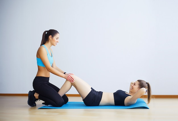 Jonge vrouw die sit-ups met hulp van vrouwelijke vriend in gymnastiek uitoefent. Premium Foto