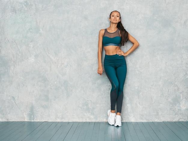 Jonge vrouw die sportkleding draagt. mooi model met perfect gebruinde lichaam. vrouwelijke poseren in de studio in de buurt van grijze muur Gratis Foto