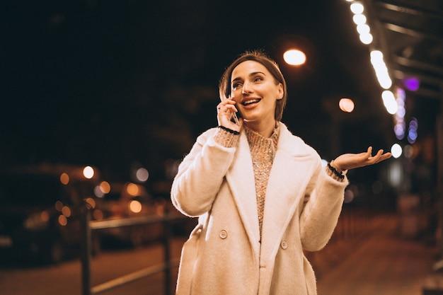 Jonge vrouw die telefoon buiten de nachtstraat met behulp van Gratis Foto