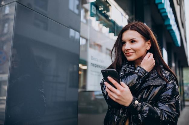 Jonge vrouw die telefoon in openlucht met behulp van Gratis Foto