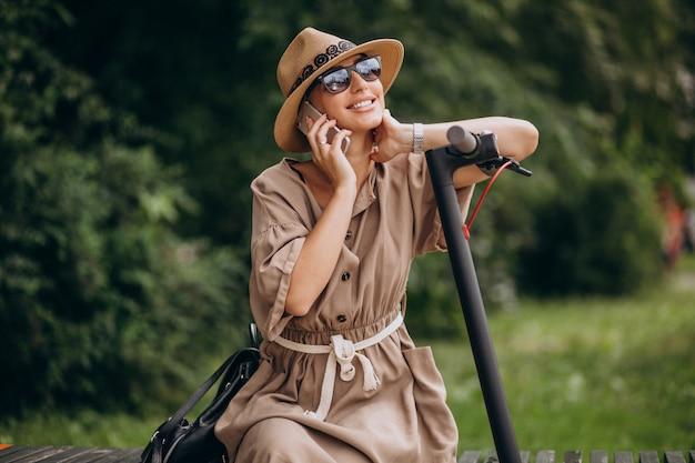 Jonge vrouw die telefoon in parkzitting op bank door de autoped met behulp van Gratis Foto