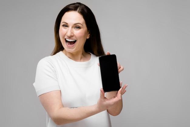 Jonge vrouw die telefoon voorstelt Premium Foto