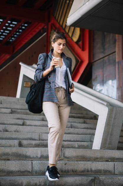 Jonge vrouw die up-down trede opstaat die beschikbare koffiekop en digitale tablet houdt Gratis Foto