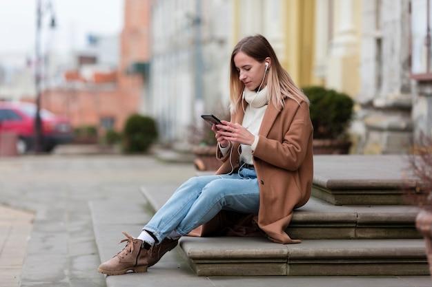 Jonge vrouw die van de muziek op haar oortelefoons in de stad geniet Gratis Foto