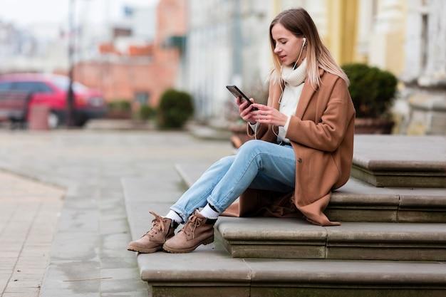 Jonge vrouw die van de muziek op oortelefoons in de stad geniet Gratis Foto