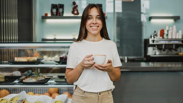 Jonge vrouw die van een koffiekop geniet Gratis Foto