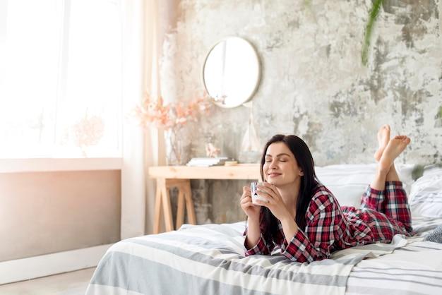 Jonge vrouw die van haar ochtend in bed geniet Premium Foto