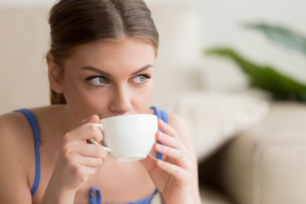 Jonge vrouw die van hete vers gezette koffie geniet Gratis Foto
