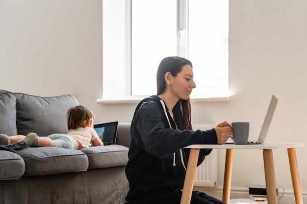 Jonge vrouw die van huis werkt. kind kijken naar tekenfilms op de tablet. werk vanuit huis Premium Foto