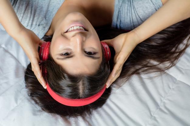 Jonge vrouw die van muziek op bed geniet. Premium Foto