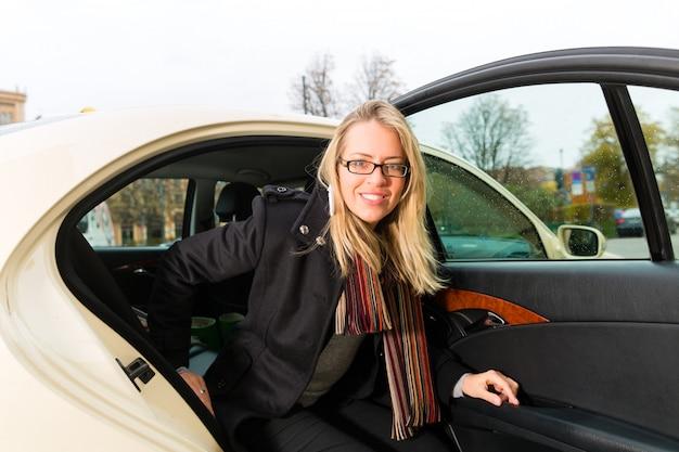 Jonge vrouw die van taxi weggaat Premium Foto