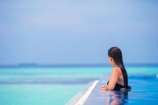 Jonge vrouw die van water en rust in openlucht zwembad geniet Premium Foto