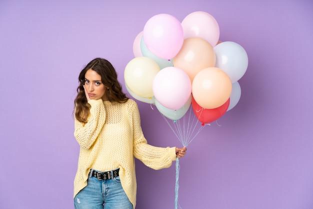 Jonge vrouw die vele ballons over op purpere muur ongelukkig en gefrustreerd vangt Premium Foto