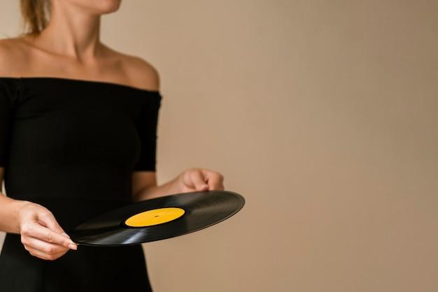Jonge vrouw die vinylschijf met exemplaar-ruimte houdt Gratis Foto