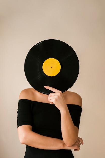 Jonge vrouw die vinylverslag over haar gezicht houdt Gratis Foto