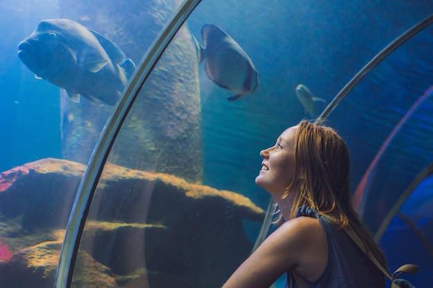 Jonge vrouw die vissen in een tunnelaquarium bekijkt. Premium Foto