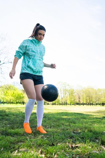 Jonge vrouw die voetbalvaardigheden met bal oefent Gratis Foto