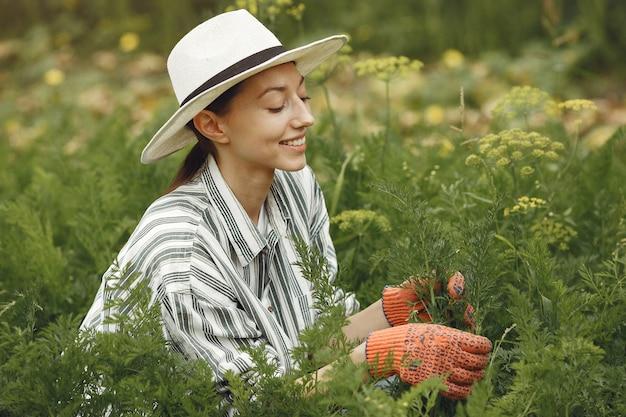 Jonge vrouw die voor planten zorgt. brunette in een hoed en handschoenen. Gratis Foto