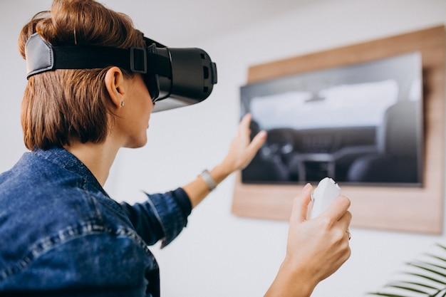 Jonge vrouw die vr-bril draagt en virtueel spel speelt dat ver gebruikt Gratis Foto