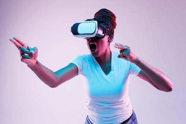 Jonge vrouw die vr-bril met neonlichten gebruikt Gratis Foto