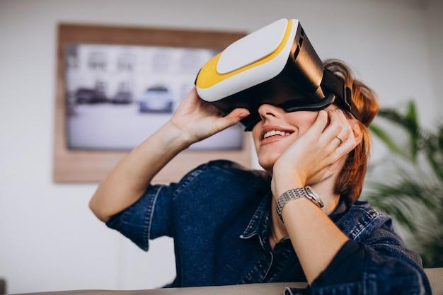 Jonge vrouw die vr glazen draagt en op virtueel spel let Gratis Foto