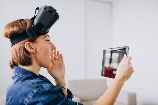 Jonge vrouw die vr glazen draagt en tablet gebruikt Gratis Foto