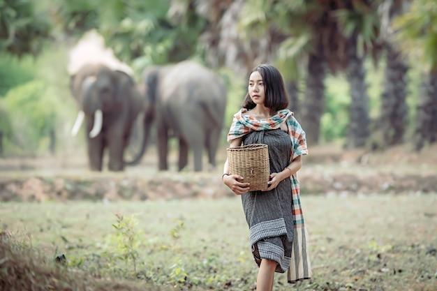 Jonge vrouw die wild voedsel zoekt terwijl het opheffen van haar olifant Premium Foto