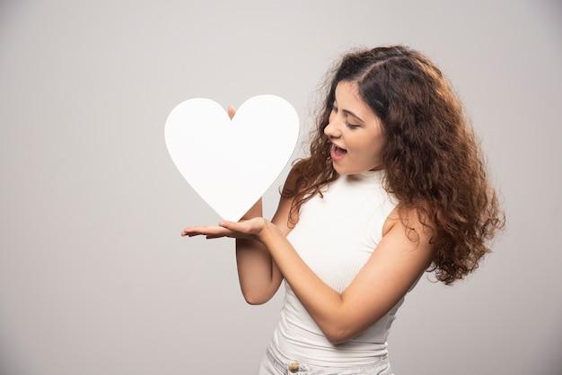 Jonge vrouw die wit handgeschept document hart bekijkt. hoge kwaliteit foto Gratis Foto