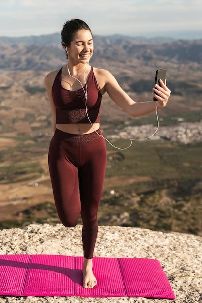 Jonge vrouw die yoga doet en telefoon met behulp van Gratis Foto