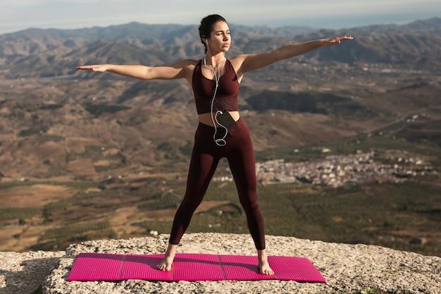 Jonge vrouw die yoga doet terwijl het luisteren muziek Gratis Foto