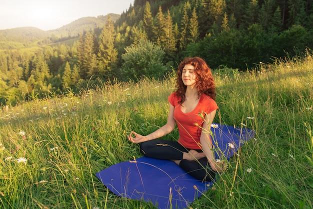 Jonge vrouw die yogaoefeningen in de aard doet Premium Foto