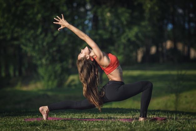 Jonge vrouw die yogaoefeningen in het park van de de zomerstad doet Premium Foto