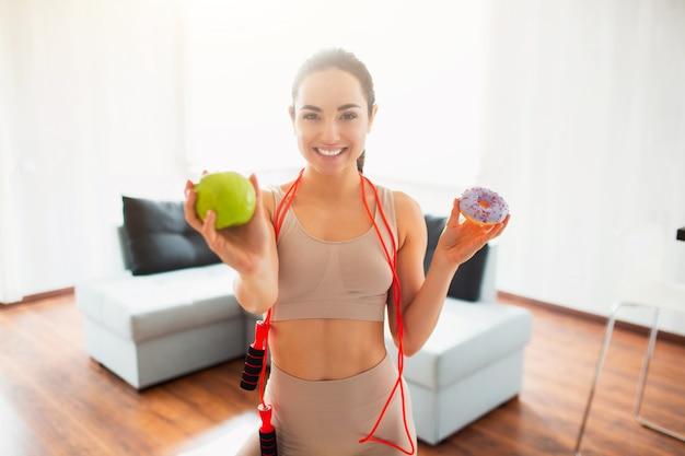 Jonge vrouw die yogatraining in ruimte doen tijdens quarantaine. het vrolijke positieve meisje houdt groene appel en hamburger in handen. moeilijke keuze. toon groene appel dichterbij. Premium Foto