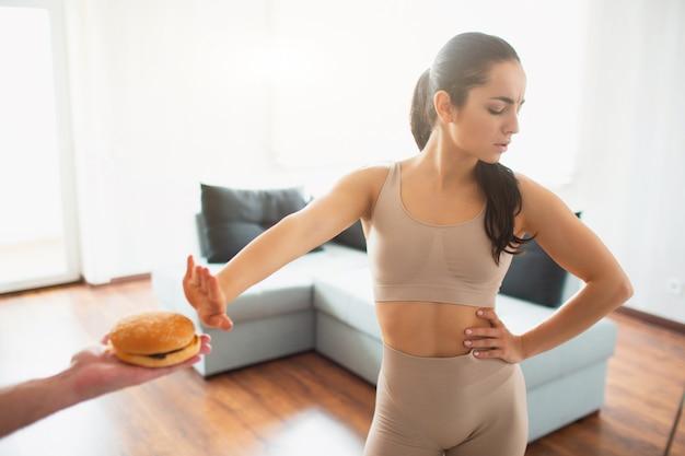Jonge vrouw die yogatraining in ruimte doen tijdens quarantaine. meisje weigert hamburger te eten. Premium Foto