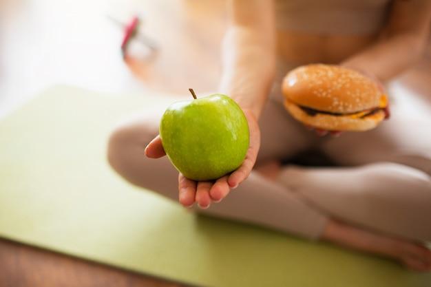 Jonge vrouw die yogatraining in ruimte doet. besnoeiingsmening van meisje die groene gezonde appel houden en hamburger vermoeien in handen. moeilijke keuze. gezonde of ongezonde levensstijl. Premium Foto