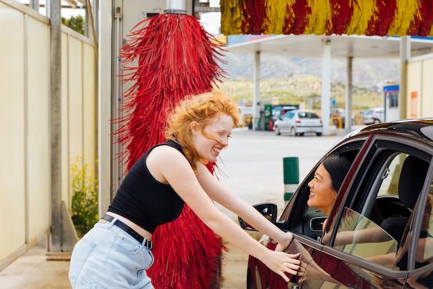 Jonge vrouw die zich bij autowasserette bevindt en aan aziatisch wijfje glimlacht dat uit autoraam kijkt Gratis Foto