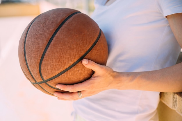 Jonge vrouw die zich bij basketbalveld bevindt Gratis Foto