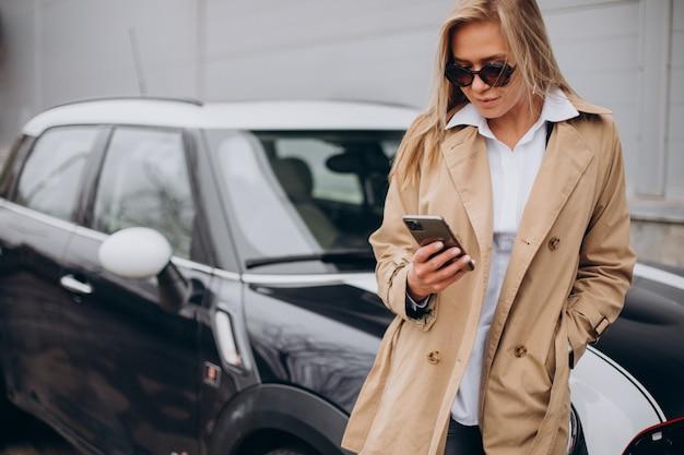 Jonge vrouw die zich door haar auto bevindt Gratis Foto