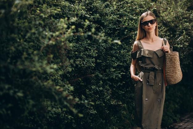 Jonge vrouw die zich in park op de groene struikachtergrond bevindt Gratis Foto