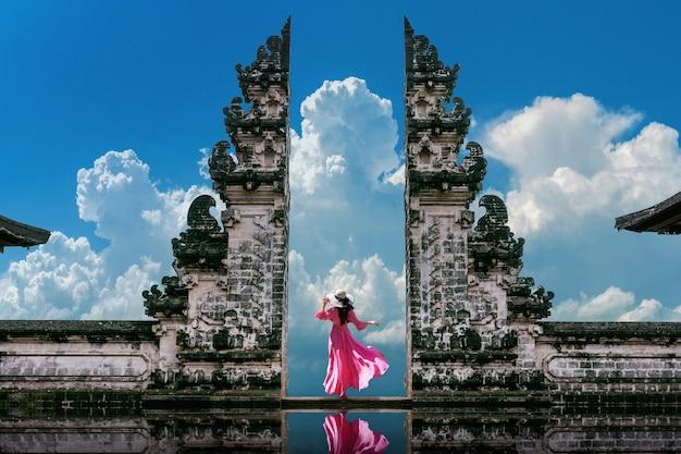 Jonge vrouw die zich in tempelpoorten bij lempuyang luhur-tempel in bali, indonesië bevindt. vintage toon Gratis Foto