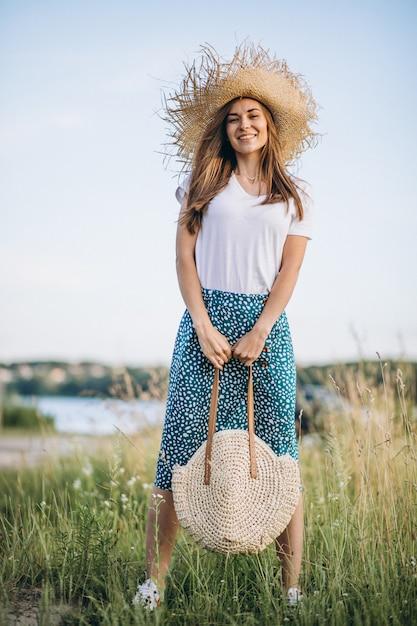 Jonge vrouw die zich met zak in grote hoed op gebied bevindt Gratis Foto