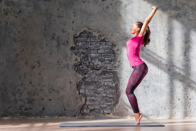 Jonge vrouw die zich op haar tiptoes tegen beschadigde muur bevindt Gratis Foto
