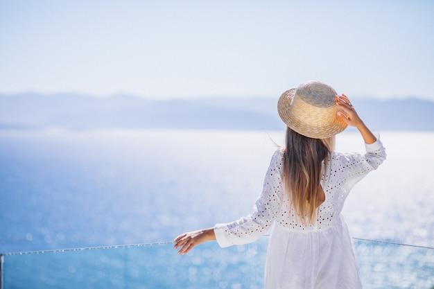 Jonge vrouw die zich van de rug bevindt en de zee bekijkt Gratis Foto