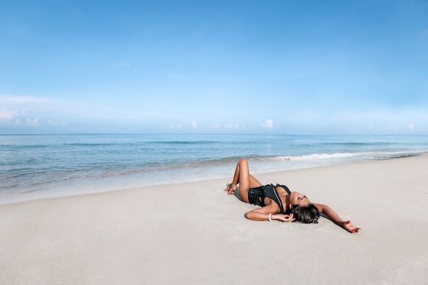 Jonge vrouw die zich voordeed op een strand Premium Foto