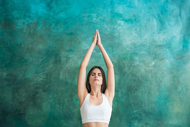 Jonge vrouw doet yoga oefeningen op groene muur Gratis Foto