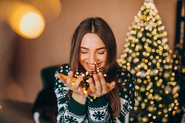 Jonge vrouw door de kerstboom met kerstmis gloeiende lichten Gratis Foto