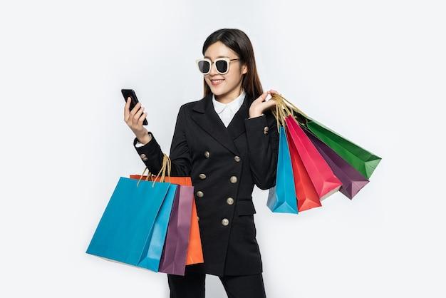 Jonge vrouw draagt een bril en winkelt op slimme telefoons Gratis Foto
