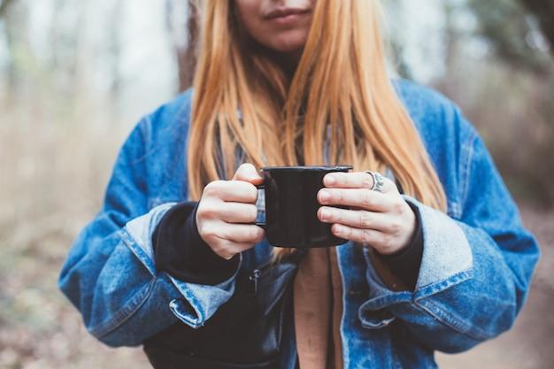 Jonge vrouw drinkt koffiekopje op de oever van het meer Gratis Foto