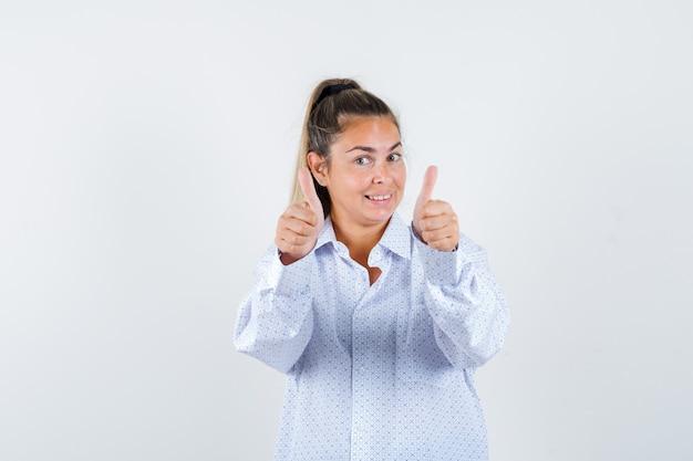 Jonge vrouw dubbele duimen opdagen in wit overhemd en vrolijk kijken Gratis Foto