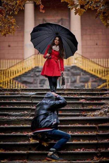 Jonge vrouw en fotograaf in het park in de regen. Premium Foto